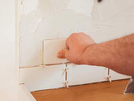 Handwerker verlegt Küchenfliesen